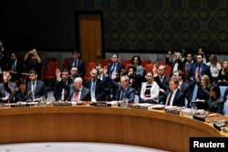 FILE - Members of the U.N. Security Council vote for cease-fire to Syrian bombing in eastern Ghouta, at U.N. headquarters in New York, Feb. 24, 2018.