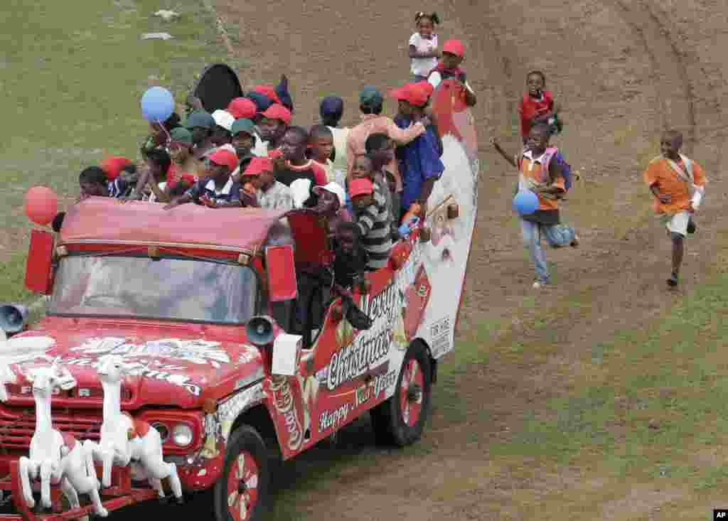 """Les enfants suivent en courant un """"Santamobile"""" (véhicule du père Noël) lors d'une fête de Noël pour les enfants défavorisés dans Maraisburg, Afrique du Sud, 7 décembre 2008."""