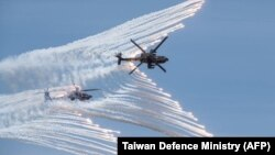This handout photo taken and released by the Taiwan Defence Ministry on July 2, 2020 shows two US-made AH-64E attack helicopters releasing flares during a drill in Taichung. (Taiwan Defence Ministry/AFP)