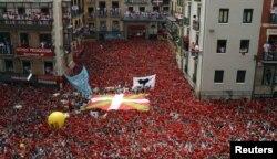 "Para peserta festival dengan gembira mengangkat syal merah mereka saat akan dimulainya Festival San Fermin di Pamplona (6/7). Peluncuran roket tradisional ""Chupinazo"" menandai dibukanya festival yang akan berlangsung hingga 14 Juli mendatang ini."