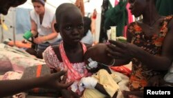 A South Sudanese nurse talks to a malnourished internally displaced orphan girl in the hospital run by Medecins Sans Frontieres (MSF) inside the camp for IDPs in Malakal, Upper Nile State, May 29, 2014.
