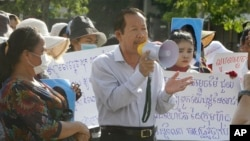 Rong Chhun, center, President of the Cambodian Trade Union Confederation, uses a megaphone during a protest near the prime minister's residence in Phnom Penh, Cambodia, Wednesday, July 29, 2020. (AP Photo/Heng Sinith)
