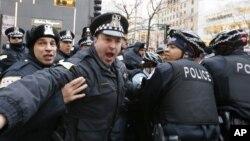 """Polisi Chicago saat mengamankan seorang pemrotes di kawasan perbelanjaan """"Magnificent Mile"""" (24/12) lalu."""