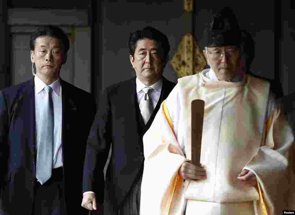 Japan's Prime Minister Shinzo Abe follows a Shinto priest as he visits Yasukuni Shrine in Tokyo, Dec. 26, 2013.
