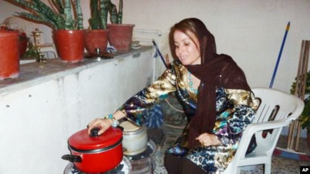 In the garage of her Tripoli house, Fatma Ghobtan checks a pot on a charcoal stove she fashioned from two car wheels after gas was cut off.