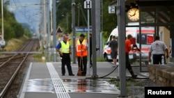 Офицер полиции стоит рядом с рабочими, моющими платформу после нападения. Железнодорожная станция в городе Залец, Швейцария. 13 августа 2016 г.