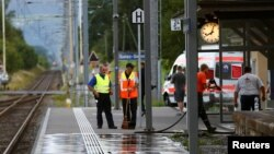 Seorang polisi Swiss berdiri di dekat seorang petugas kebersihan yang sedang membersihkan lokasi pasca serangan yang dilakukan oleh seorang pemuda 27 tahun di stasiun kereta kota Salez, Swiss, 13 Agustus 2016 (Foto: dok).