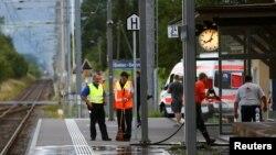Một cảnh sát Thụy Sĩ đứng gần các nhân viên dọn dẹp nhà ga sau khi người đàn ông Thụy Sĩ 27 tuổi tấn công hành khách trên một chuyến tàu ở nhà ga thị trấn Salez, ngày 13 tháng 8 năm 2016.