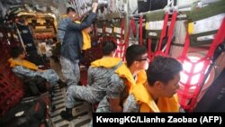 Republic of Singapore Air Force personnel (RSAF) servicemen on board a C-130 aircraft participating in the search and locate (SAL) operation for missing AirAsia flight QZ8501 at sea, Dec. 29, 2014.