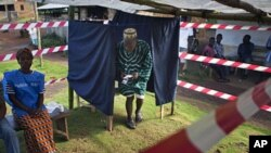 A Liberian man exits a polling booth for the presidential election run-off at Klay town just outside the capital Monrovia, November 8, 2011