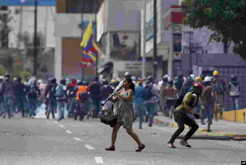 در جریان درگیری های تظاهرکنندگان و نیروهای دولتی کاراکاس ونزوئلا، زنی در حال فلوت زدن است.