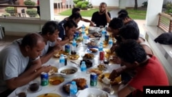 FILE - Indonesian sailors, who were kidnapped by the Abu Sayyaf militant group, eat a meal at a local government official's house after they were released from captivity in Jolo, Sulu in southern Philippines, May 2, 2016.