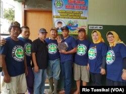 Pengurus dan anggota Bank Sampah Nuruf Fikri, Gedebage, Bandung, menunjukkan paving block dari limbah plastik yang diproduksi swadaya, Gedebage, Bandung, 7 Februari 2019. (VOA/Rio Tuasikal)