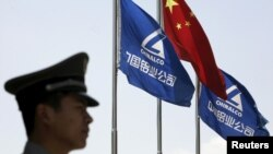 FILE - A security guard stands in position in front of the company's and Chinese flags outside the headquarters of Aluminum Corp of China (Chinalco) in Beijing in this June 5, 2009 file photo.