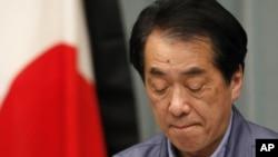 日本首相菅直人在记者会上,旁边是镶了黑边的日本国旗