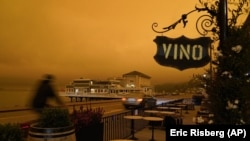FILE - In this Sept. 9, 2020, file photo, a bicyclist rides past a seating area outside a wine bar as smoke from wildfires darken the morning sky in Sausalito, California.