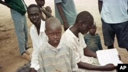 FILE - Sudanese boys pass the time in the Kakuma camp, in northern Kenya, April 24, 2000. Over 20,000 boys who were displaced or orphaned during two decades of civil war endured many hardships as they traveled on foot to refugee camps in Ethiopia and Kenya.