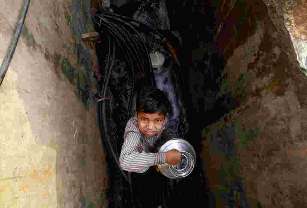 Un niño indio sostiene un recipiente tras recolectar agua en las afueras de un barrio de Bombay, India.