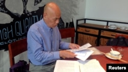 Xu Xiaoshun, the father of activist Wu Gan looks through documents about his son's case in a restaurant in Jiangsu Province.
