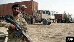 Binh sĩ bán quân sự Pakistan canh gác bên cạnh xe tải chở nhiên liệu của NATO tại thị trấn biên giới Chamam