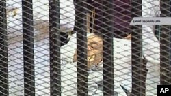 Former Egyptian President Hosni Mubarak is wheeled into a holding cell in the court room in the police academy on the outskirt of the capital Cairo, where he faces murder charges, August 3, 2011
