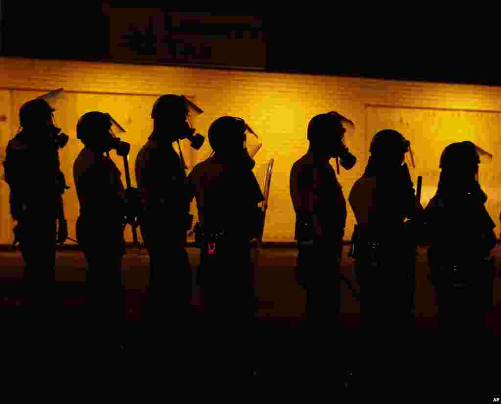 Police wait to advance after tear gas was used to disperse a crowd during a protest for Michael Brown in Ferguson, Missouri, Aug. 17, 2014.