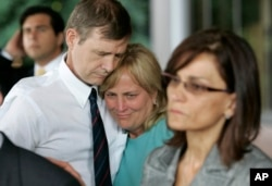 FILE - Andrew Goddard, whose son was wounded during a deadly 2007 shooting at Virginia Tech in 2007, comforts another parent during a 2008 news conference announcing an $11 million state settlement with victims' families.
