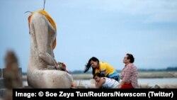 یک خانواده در حال نیایش در مقابل مجسمه بی سر بودا در معبد گمشده ای که در اثر خشکسالی از زیر آب بیرون آمده است. اوت ۲۰۱۹