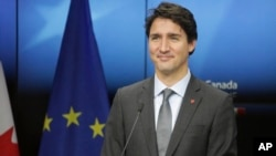 FILE - Canadian Prime Minister Justin Trudeau prepares to address a media conference at the end of an EU-Canada summit at the European Council building in Brussels.
