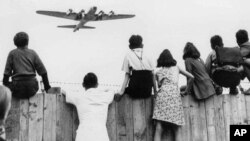 西柏林的儿童在滕珀尔霍夫机场围栏上看美国飞机运来补给