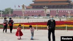 戴着口罩的北京市民在天安门广场为五一劳动节建起的花坛旁散步。(2020年4月29日)