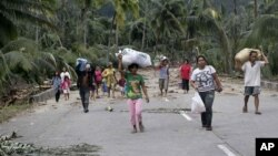 Residents evacuate to higher grounds at the flash flood-hit village of Andap, New Bataan township, Compostela Valley in southern Philippines, December 5, 2012.