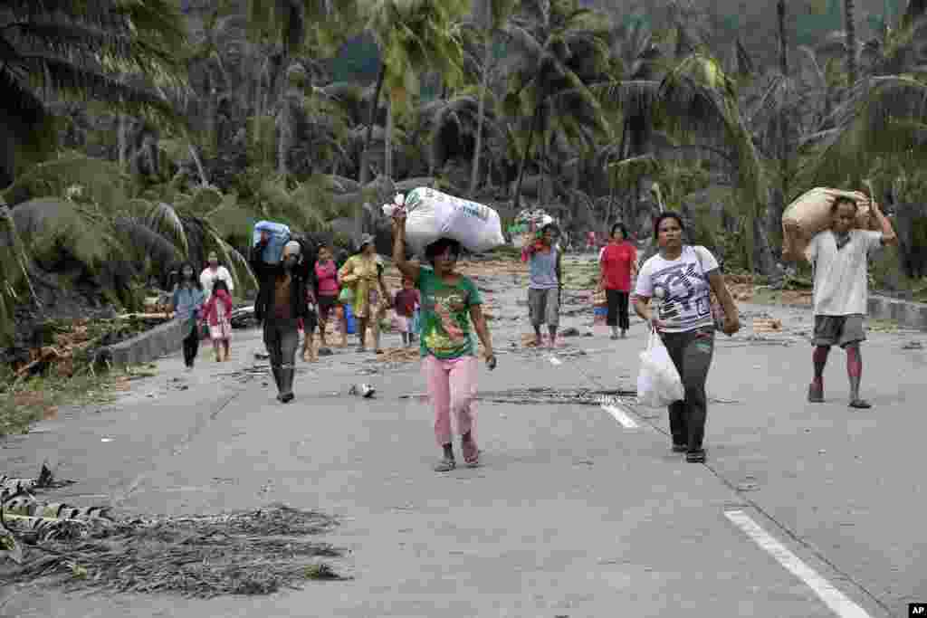 Residents evacuate to higher grounds at the flash flood-hit village of Andap, New Bataan township, Compostela Valley, Philippines, December 5, 2012.