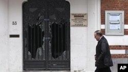 Man walks past damaged door of Reda mosque in Brussels, Belgium March 13, 2012.
