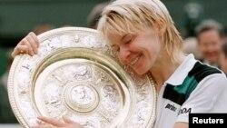 Jana Novotna memeluk Piala Wimbledon setelah mengalahkan Nathalie Tauziat dari Perancis di final Tunggal Putri Wimbledon, 4 Juli 1998. (Foto:Dok)
