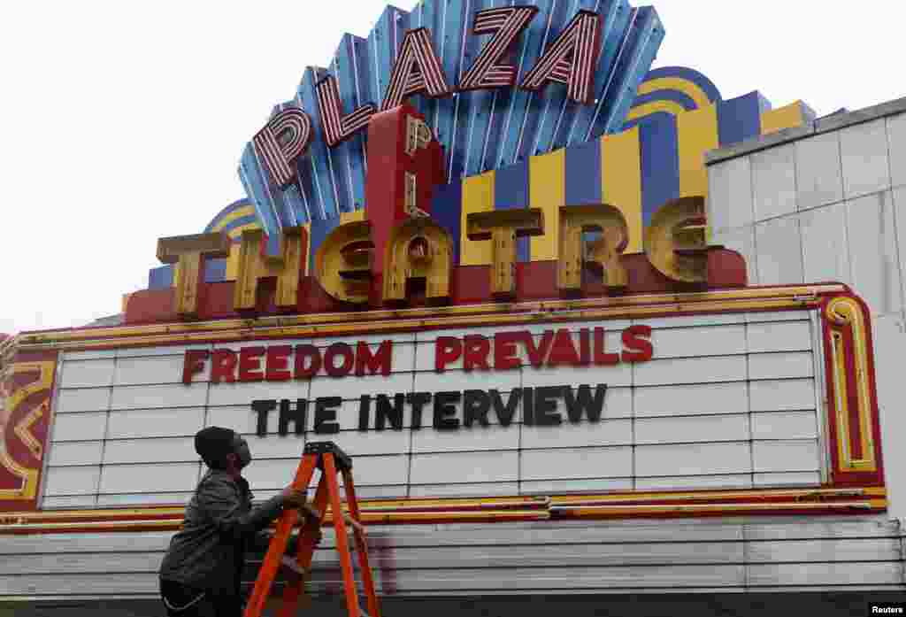 "General Manager Brandon Delaney looks up at the marquee sign after the announcement that the Plaza Theatre would be showing the movie ""The Interview"" beginning Christmas Day in Atlanta, Georgia. Sony Pictures said it will release ""The Interview"" to a limited number of theaters on Dec. 25, less than a week after it canceled the comedy's release following a devastating cyberattack blamed on North Korea."