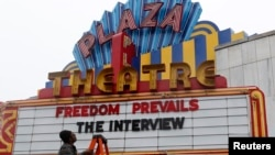 "General Manager Brandon Delaney looks up at the marquee sign after the announcement that the Plaza Theatre would be showing the movie ""The Interview"" beginning Christmas Day in Atlanta, Georgia December 23, 2014. Sony Pictures said on Tuesday it will rel"