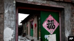 "Clothes hang from a green entrance door of a single-story brick house, known as a ""black jail"" in Beijing, Feb. 5, 2013."