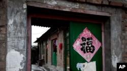Quần áo treo trước cửa ra vào của căn nhà gạch một tầng, được biết đến như một 'nhà tù đen' ở Bắc Kinh.