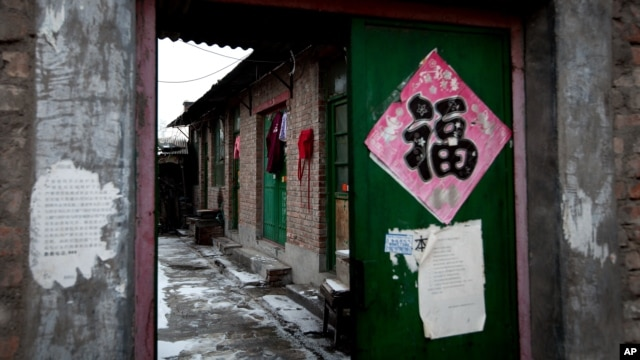 "Baju terlihat digantungkan di sebuah pintu masuk berwarna hijau di sebuah rumah batu bata, 5 Februari 2013. (AP Photo/Andy Wong). Rumah ini  di kalangan pemerintah Beijing dikenal sebagai ""penjara hitam"", yang dilaporkan sering dipergunakan oleh pejabat lokal untuk memenjarakan warga setempat secara ilegal."