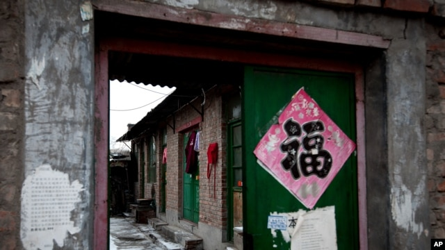 """Clothes hang from a green entrance door of a single-story brick house, known as a """"black jail"""" in Beijing, Feb. 5, 2013."""