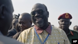 Ramadan Hassan Lako, head of a delegation of South Sudan's armed opposition, smiles upon arrival to the country's capital Juba after two year's in exile, Dec. 21, 2015.