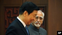 Indian Vice President Hamid Ansari, right, and Chinese Vice President Li Yuanchao attend a signing ceremony at the Great Hall of the People in Beijing Monday, June 30, 2014.