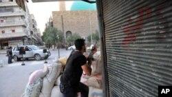 ສະມາຊິກກຸ່ມກະບົດຜູ້ນຶ່ງ ກໍາລັງຕັ້ງທ່າຈະຍິງຍົນເຮບີຄອບເຕີ ຂອງທະຫານລັດຖະບານກໍາລັງ ບິນເຫວີ່ນຢູ່ເທິງເມືອງ Aleppo ທາງພາກເໜືອຂອງຊີເຣຍໃນວັນທີ 23 ກໍລະກົດ, 2012.