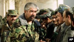 FILE - Rashid Dostum shakes hands with local residents in Shebergan, Afghanistan,, Dec. 27 , 2001.