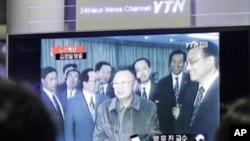 人们在首尔火车站观看金正日访问中国的新闻