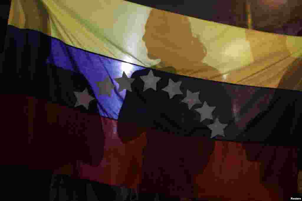 Shadows are cast on a Venezuelan national flag during a protest supporting Venezuelan opposition leader Henrique Capriles in Panama City April 15, 2013.