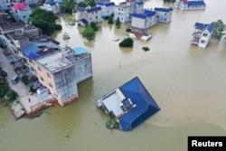 中国江西省鄱阳湖附近村庄被淹一房屋被洪水冲倒。(2020年7月13日)