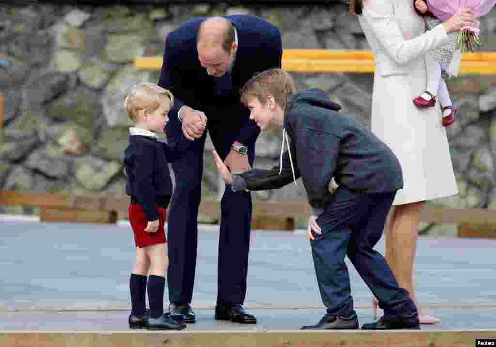 Daniel Bachman (R), who presented flowers to the Royal family, tries to high-five Britain's Prince George (L) while Prince William looks on as they arrive to board a floatplane for their official departure from Canada in Victoria, British Columbia, Canada, Oct. 1, 2016.