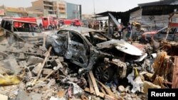 A destroyed car is seen at the site of a car bomb attack in Jamila market in Sadr City district of Baghdad, Iraq, Aug. 28, 2017.